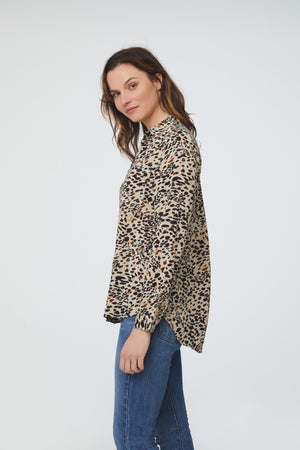 side view of woman wearing a light animal print, long sleeve, button-down blouse with a single chest pocket and drop back hem