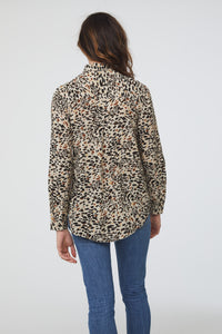 back view of woman wearing a light animal print, long sleeve, button-down blouse with a single chest pocket and drop back hem
