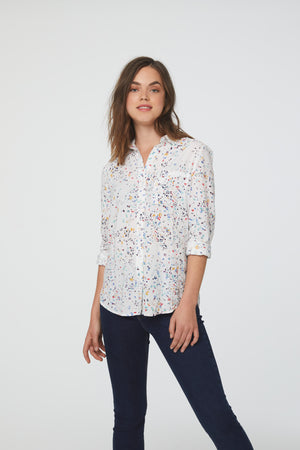 woman wearing a white, vibrant confetti print, long sleeve, button-down blouse with single chest pocket and drop back hem