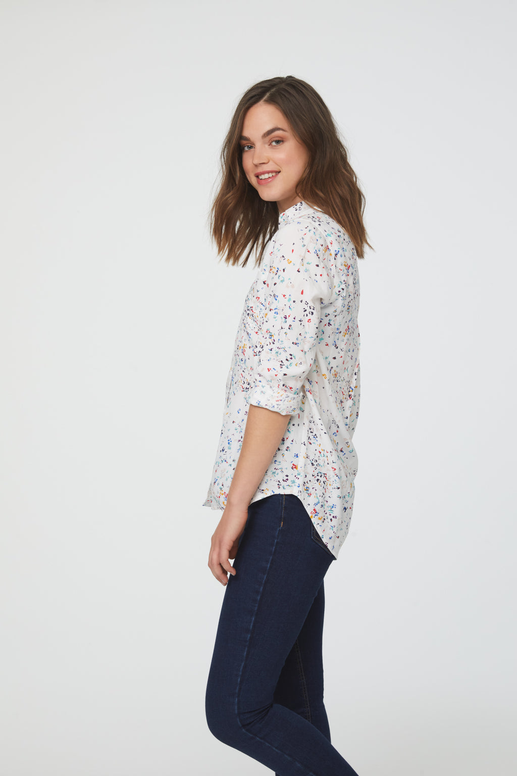 side view of woman wearing a white, vibrant confetti print, long sleeve, button-down blouse with single chest pocket and drop back hem