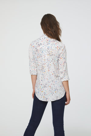 back view of woman wearing a white, vibrant confetti print, long sleeve, button-down blouse with single chest pocket and drop back hem