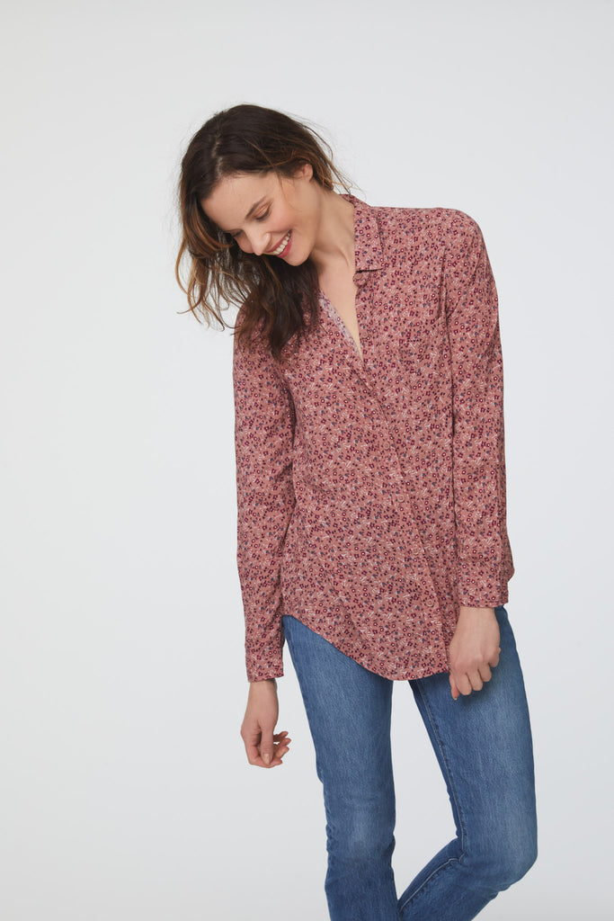 woman wearing a pink vintage-floral print, long sleeve, button-down blouse with a single chest pocket and drop back hem