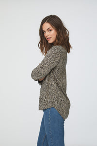 side view of woman wearing a cheetah print, long sleeve, button-down blouse with single chest pocket and drop back hem