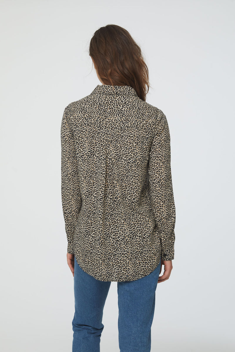 back view of woman wearing a cheetah print, long sleeve, button-down blouse with single chest pocket and drop back hem