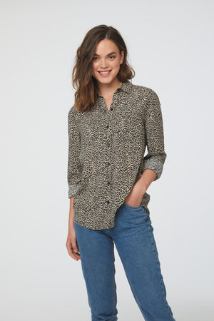 woman wearing a cheetah print, long sleeve, button-down blouse with single chest pocket and drop back hem