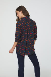 woman wearing a long sleeve, button front navy blouse with multi-color dachshund dog print and single chest pocket