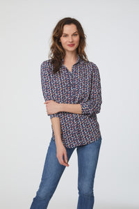 woman wearing a blue, bird print, long sleeve, button-down blouse with a single chest pocket and drop back hem