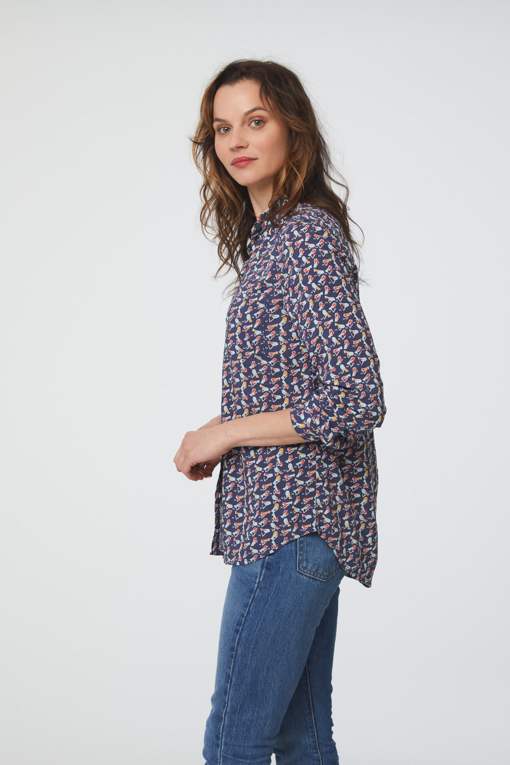 side view of woman wearing a blue, bird print, long sleeve, button-down blouse with a single chest pocket and drop back hem