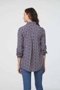 back view of woman wearing a blue, bird print, long sleeve, button-down blouse with a single chest pocket and drop back hem