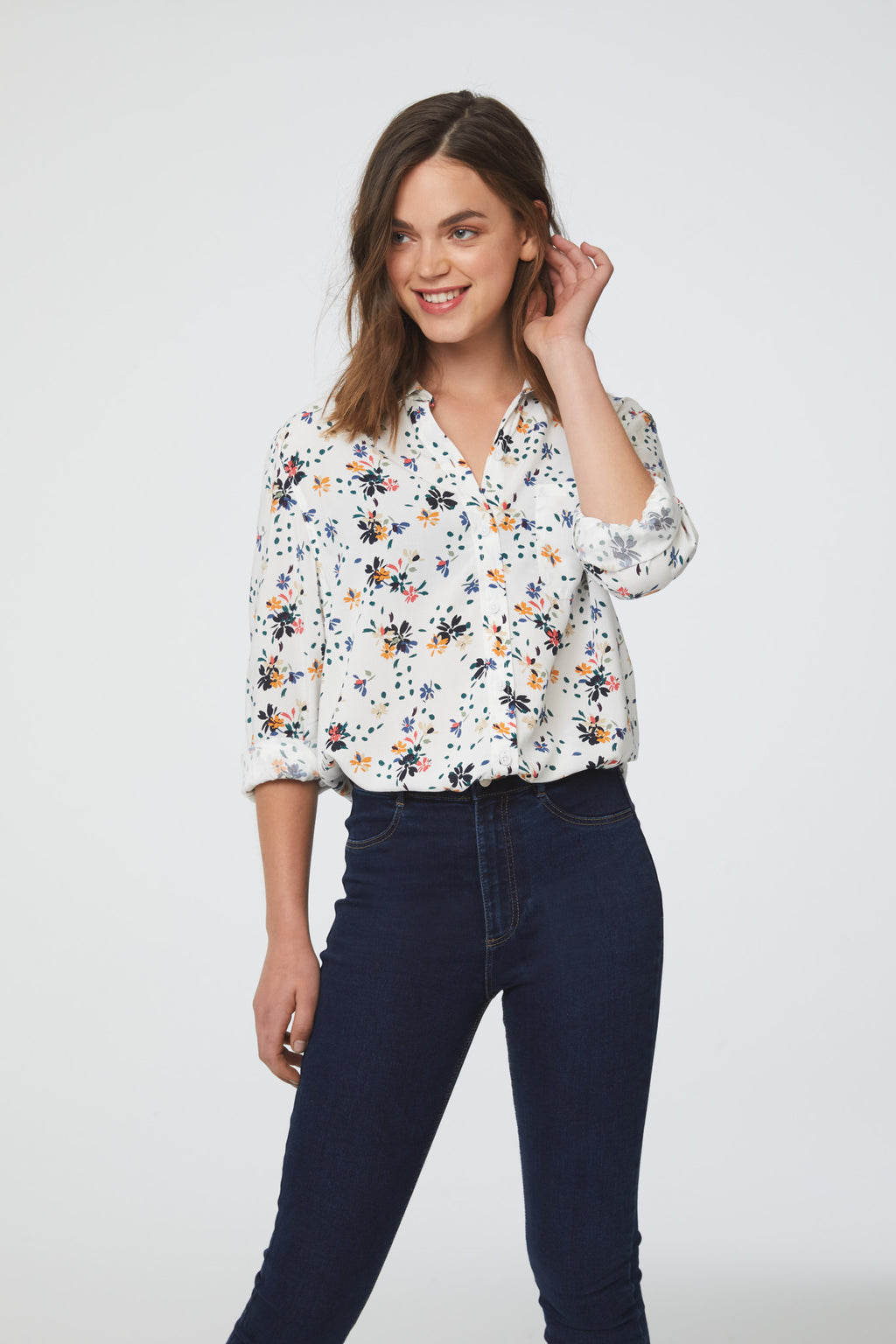 woman wearing a white floral print, long sleeve, button-down blouse with single chest pocket and drop back hem