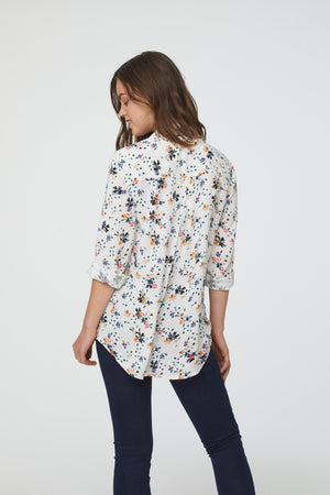 back view of woman wearing a white floral print, long sleeve, button-down blouse with single chest pocket and drop back hem