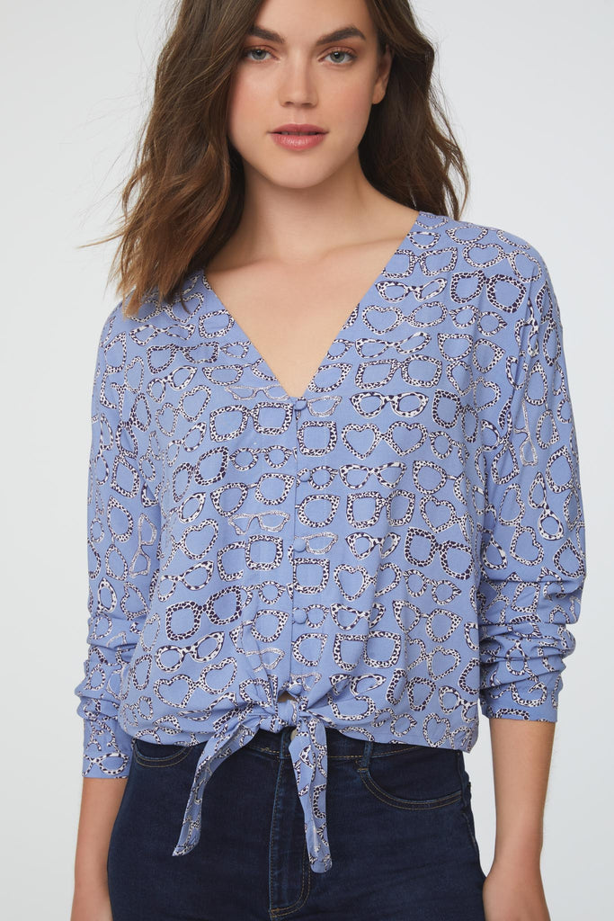 Woman wearing a blue, silky, long sleeve, button front, v-neck, eyeglass print blouse with self tie front and drop shoulder