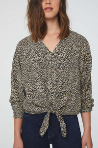 woman wearing a silky, long sleeve, button front, v-neck, cheetah-print blouse with self tie front and drop shoulder