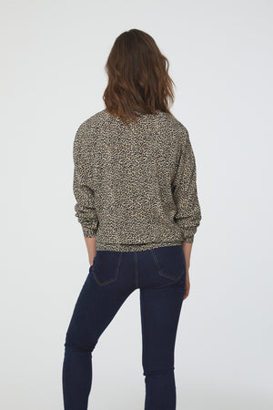 back view of silky, long sleeve, button front, v-neck, cheetah-print blouse with self tie front and drop shoulder