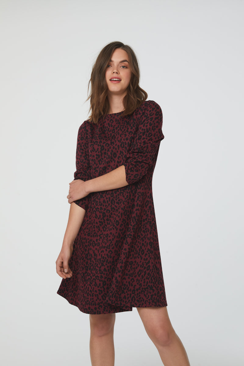 woman wearing a-line, crew neck dress in maroon and black animal print with bracelet sleeves