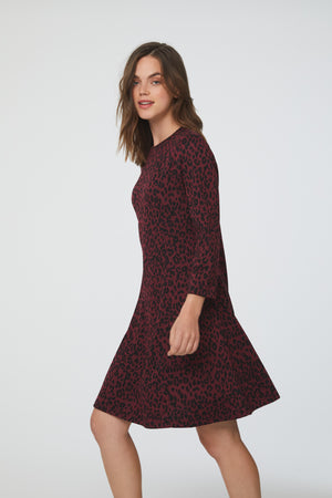 Side view of woman wearing a-line, crew neck dress in maroon and black animal print with bracelet sleeves