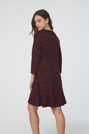 back view of Side view of woman wearing a-line, crew neck dress in maroon and black animal print with bracelet sleeves