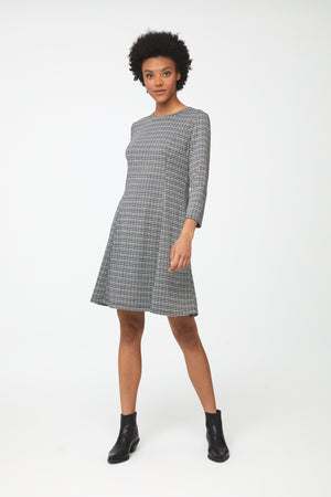 Woman wearing knee length, a-line, crew neck dress in classic checkered print with bracelet sleeves