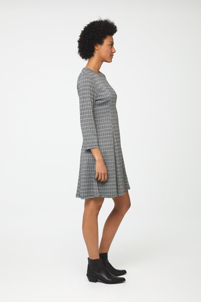 Side view Woman wearing knee length, a-line, crew neck dress in classic checker print with bracelet sleeves