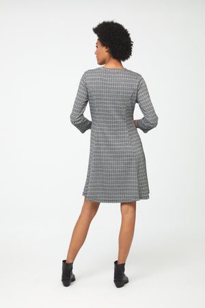 Back view of woman wearing knee length, a-line, crew neck dress in classic checkered print with bracelet sleeves