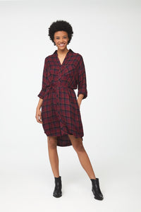 Woman wearing deep red plaid, long sleeve, collared, button-front shirt dress with self-belt