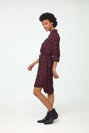 Side view of woman wearing deep red plaid, long sleeve, collared, button-front shirt dress with self-belt