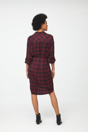 back view of woman wearing deep red plaid, long sleeve, collared, button-front shirt dress with self-belt