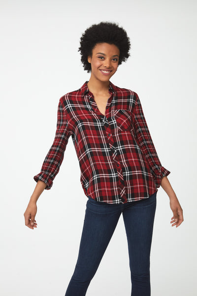 Woman wearing long sleeve, button-front red plaid shirt with white and black accents