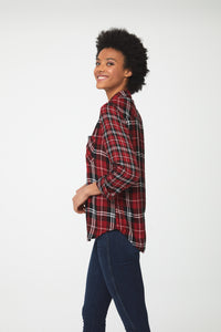 Side view woman wearing long sleeve, button-front red plaid shirt with white and black accents