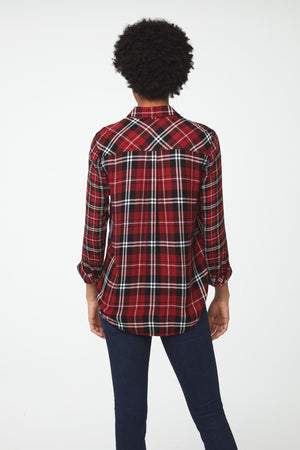 Back view woman wearing long sleeve, button-front red plaid shirt with white and black accents