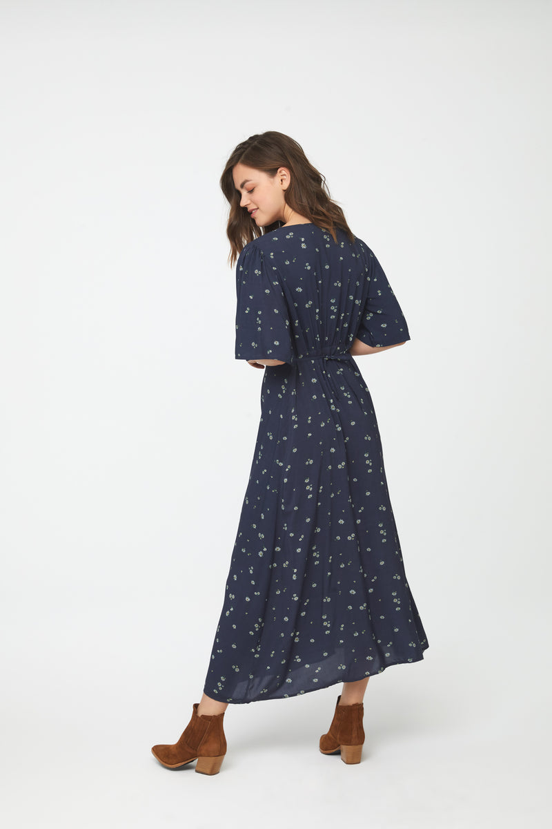 back view of woman wearing navy-blue floral, A-line midi dress with front button v-neck and short flutter sleeves