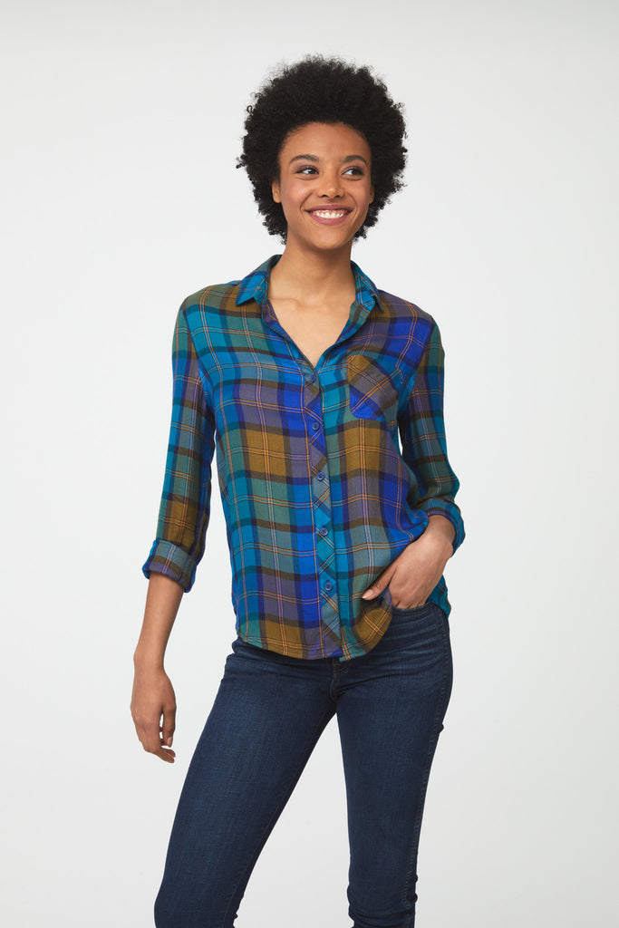 Woman wearing a long sleeve button front, plaid shirt. Plaid pattern is a mix of greens, blues, and golden yellow colors