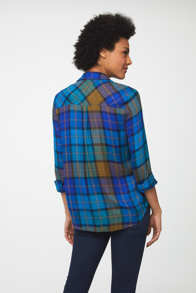 The back of a woman wearing a long sleeve plaid shirt. Plaid pattern is a mix of greens, blues, and golden yellow colors