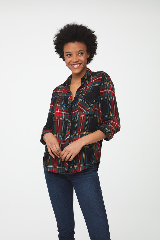 Woman wearing a long sleeve, button-down plaid shirt in forest green with red accents and a single chest pocket