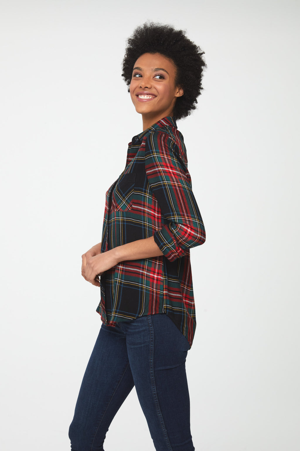 Side view of woman wearing a cuffed long sleeve, button-down plaid shirt in forest green with red accents and a single chest pocket