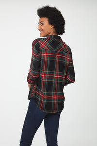 Back view of woman wearing a cuffed long sleeve, button-down plaid shirt in forest green with red accents and drop back hem