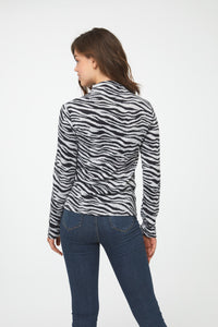 Back of woman wearing a long sleeve black and white zebra-print mockneck sweater