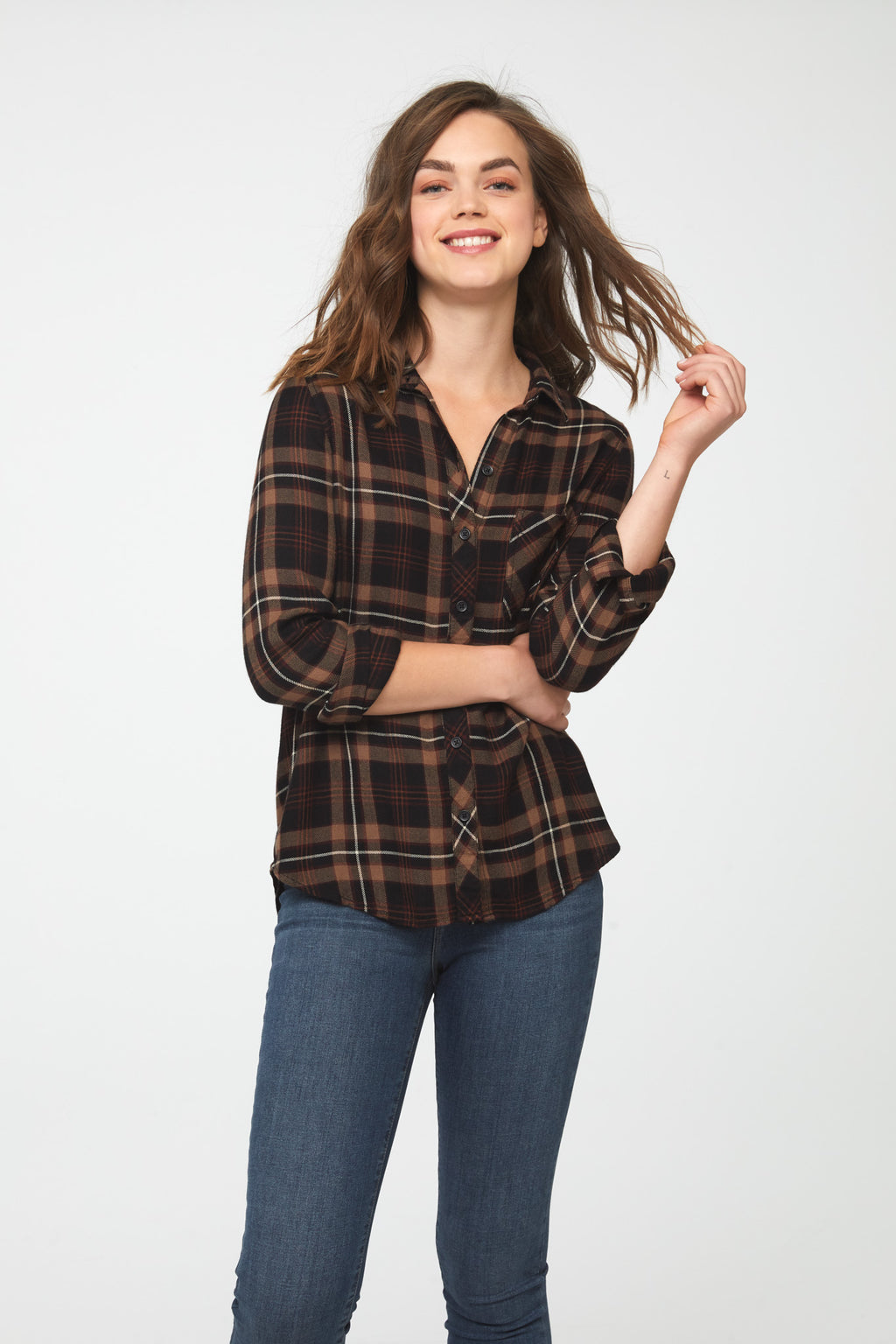 Woman wearing a long sleeve, button-down, earth-toned plaid shirt with a single chest pocket