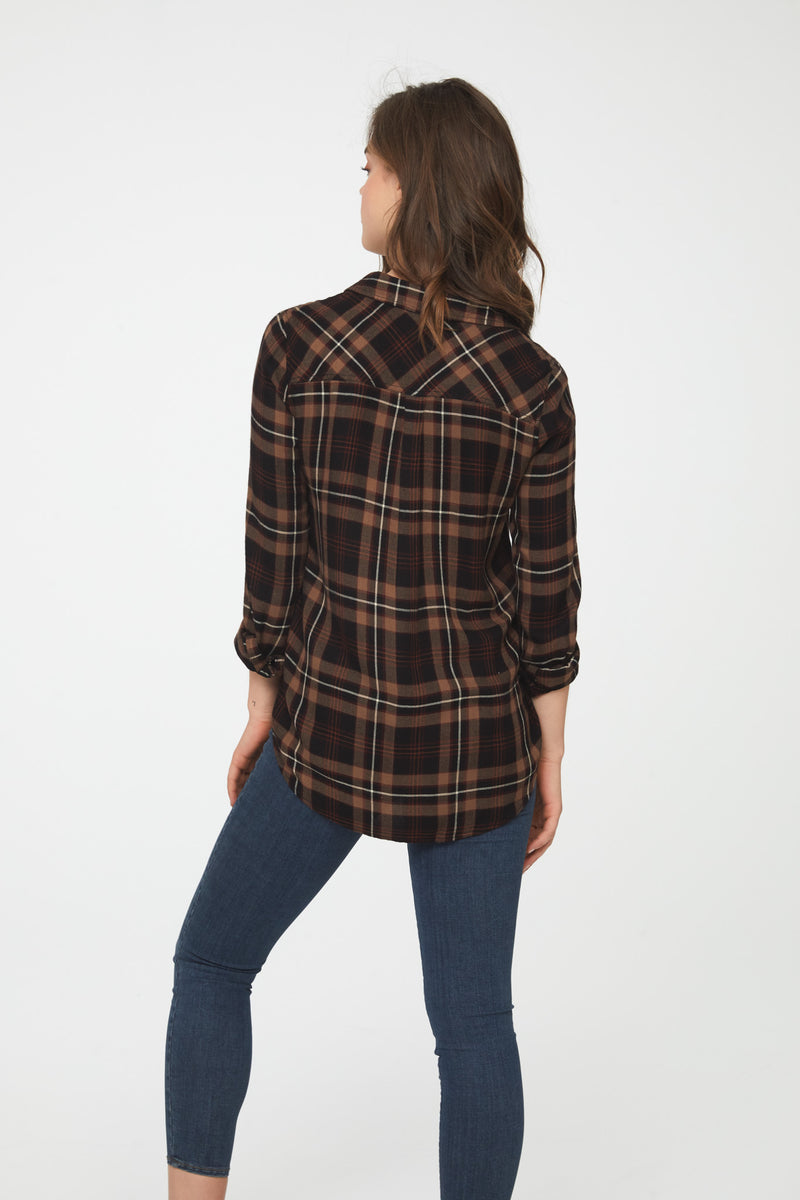 Back view of woman wearing a long sleeve, button-down, earth-toned plaid shirt with drop hem back