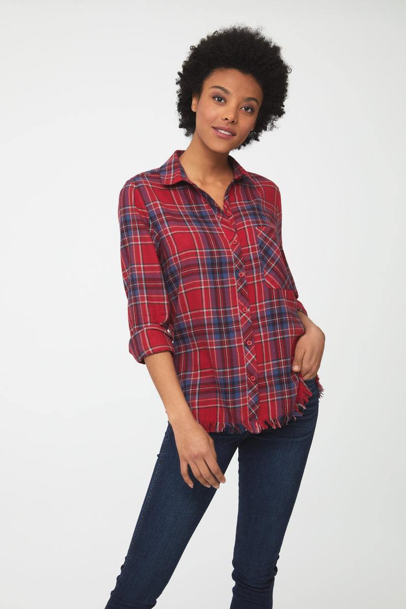 Woman wearing long sleeve, button front flannel shirt in red, white, and blue plaid with frayed hem detailing
