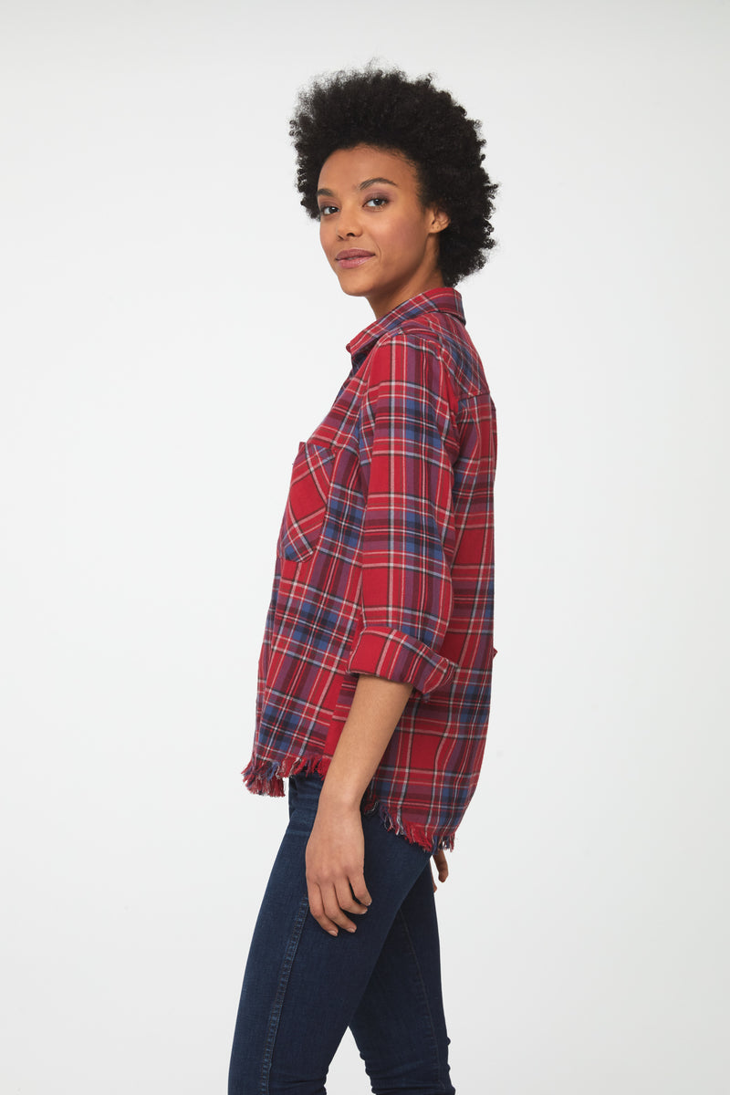 Side view of Woman wearing long sleeve, button front flannel shirt in red, white, and blue plaid with frayed hem detailing