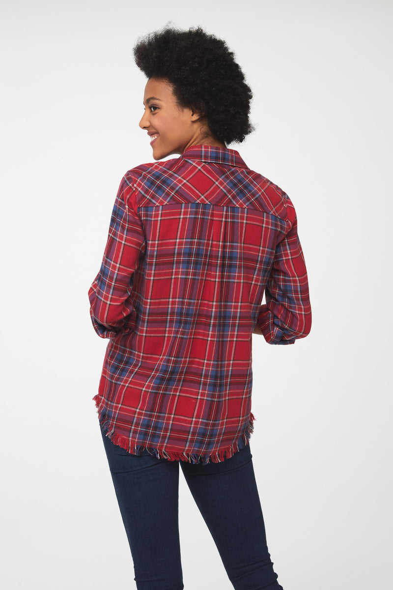 Back view of Woman wearing long sleeve, button front flannel shirt in red, white, and blue plaid with frayed hem detailing