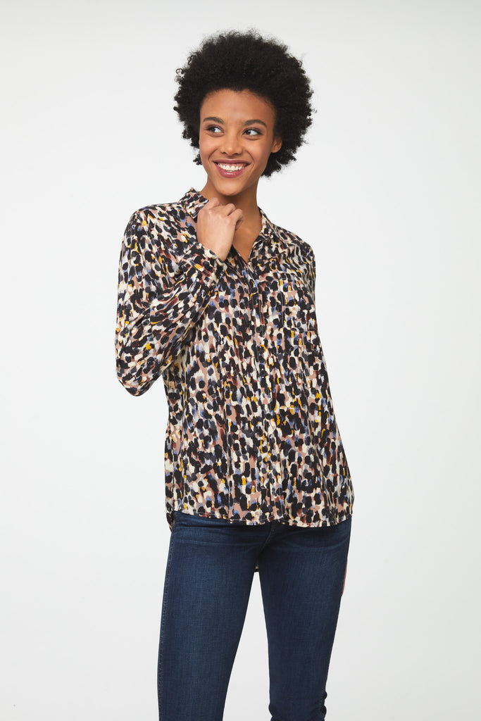woman wearing a long sleeve, button-down blouse in paint-dot print with a single chest pocket and drop back hem