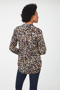 back view of woman wearing a long sleeve, button-down blouse in paint-dot print with a single chest pocket and drop back hem