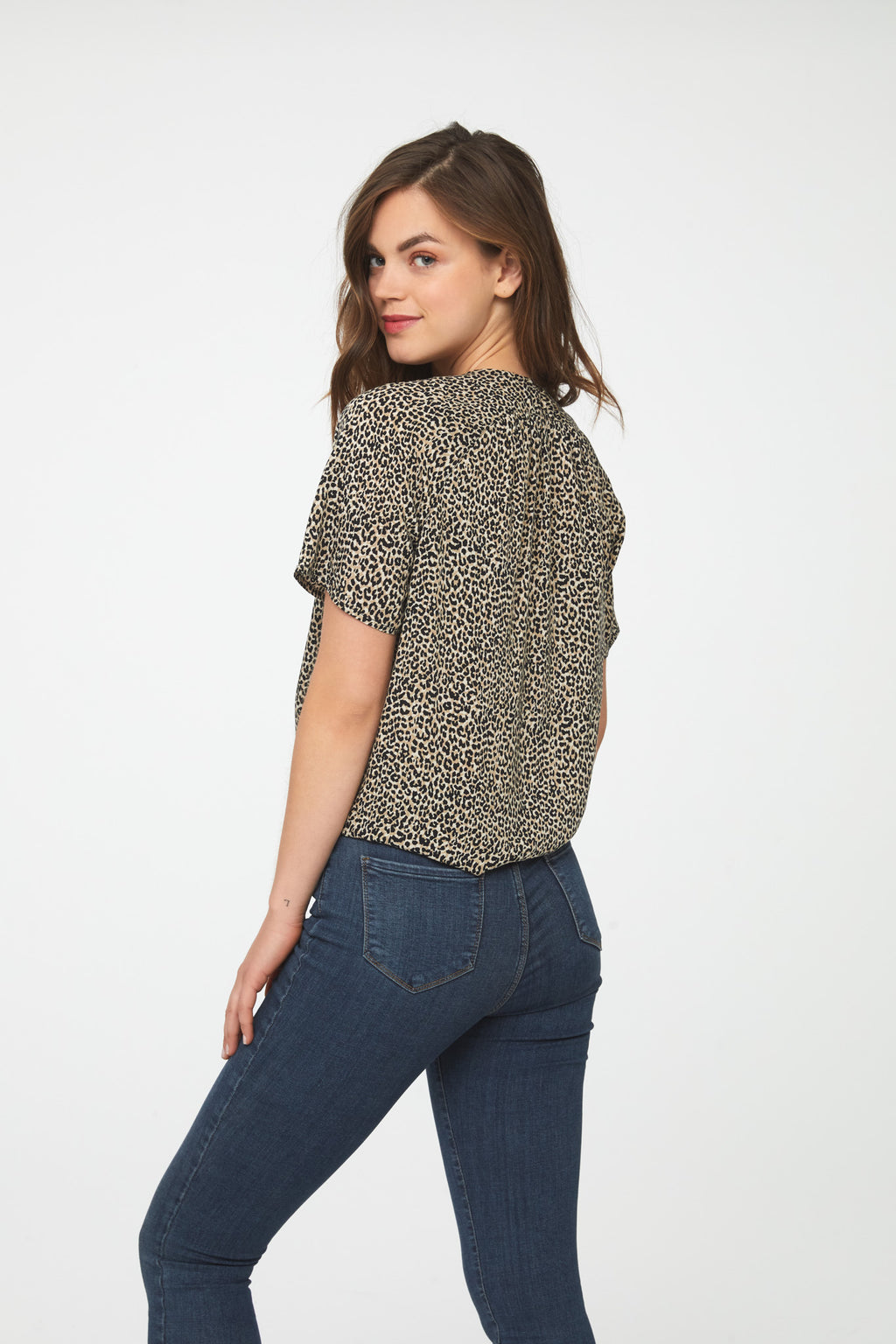 back of woman wearing a silky, short sleeve, button front v-neck blouse in leopard print with self tie front and drop shoulder
