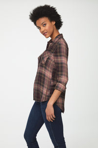 side view of woman wearing a long sleeve button-down shirt in pink and brown plaid with single chest pocket and drop back hem