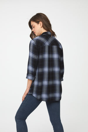 back of woman wearing a long sleeve, navy blue button-down plaid shirt with single chest pocket