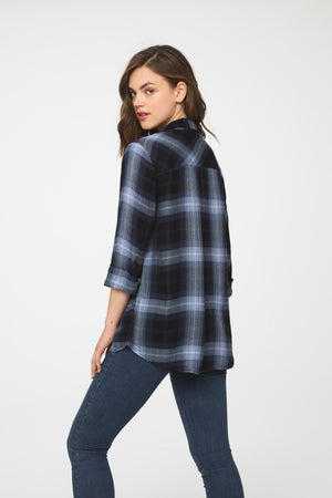 back of woman woman wearing a long sleeve, navy blue button-down plaid shirt with single chest pocket