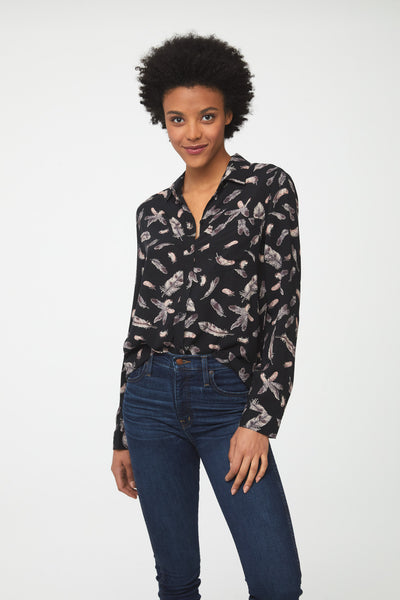woman wearing a black, long sleeve button-down blouse with feather print, single chest pocket and drop back hem