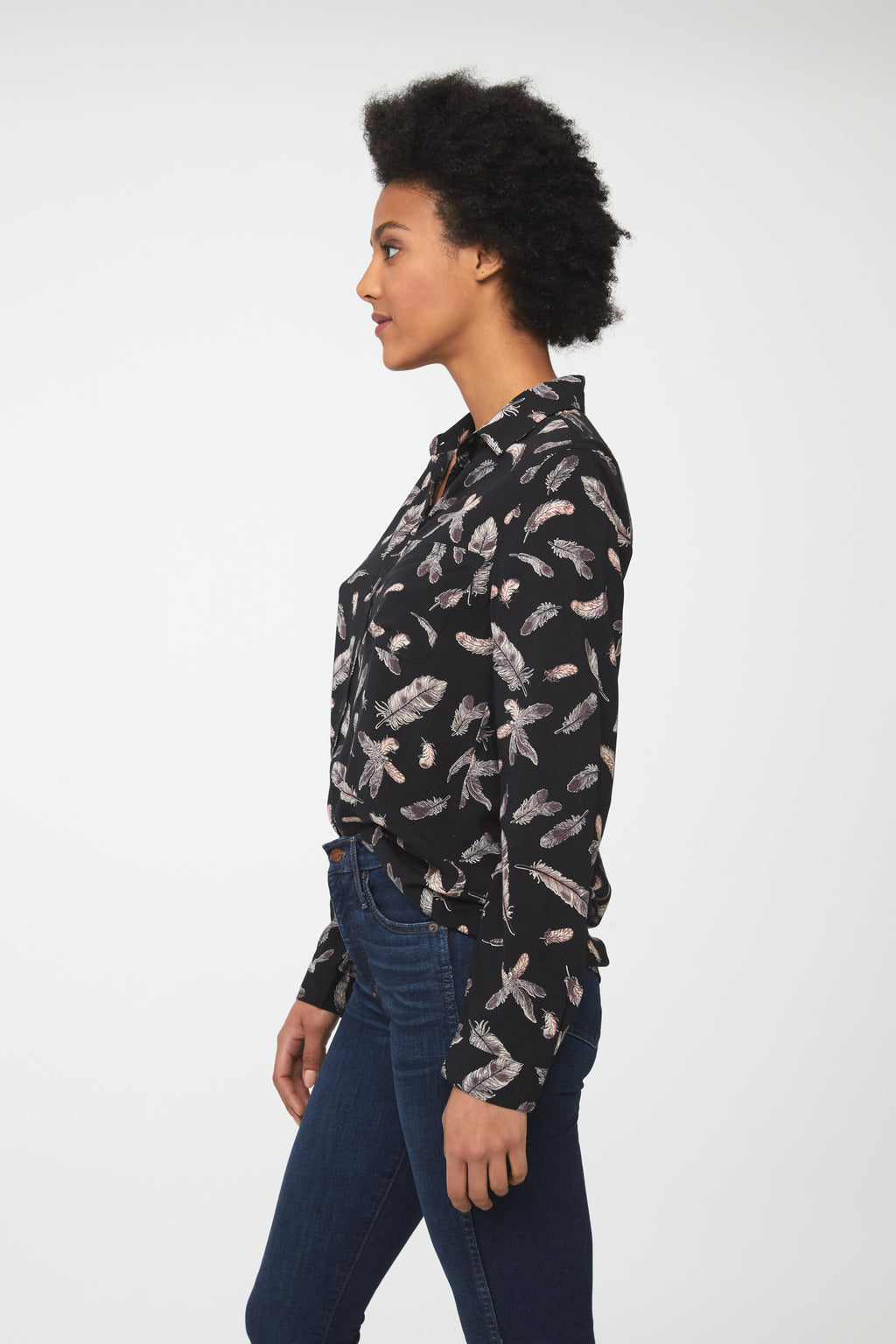 side view of woman wearing a black, long sleeve button-down blouse with feather print, single chest pocket and drop back hem